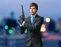 Agent with gun or pistol in hands at dusk Royalty Free Stock Images