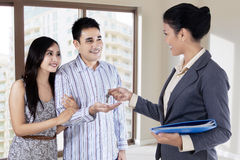 The agent handed the keys to young couple Royalty Free Stock Photography