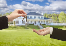 Agent Handing Over House Keys in Front of New Home Stock Photography