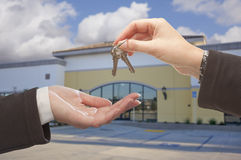 Agent Handing Over the Keys in Front of Business Office. Real Estate Agent Handing Over the Keys in Front of Vacant Business Office Royalty Free Stock Photography