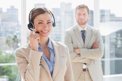 Agent heureux de centre d'appel avec le collègue derrière elle Images libres de droits