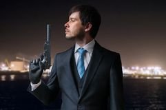 Agent or hitman holds pistol with silencer in hand at night Stock Images