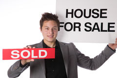 Agent holding a House For Sale and Sold sign Royalty Free Stock Photo