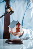 Agent Holding Miniature House with Wooden Gavel Stock Photo