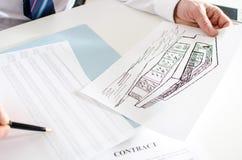 Agent immobilier analysant la planification financière d'une maison Image libre de droits