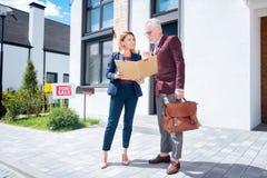 agent immobilier aux cheveux blonds venant à la maison de luxe pour la vendre à l'homme d'affaires images libres de droits
