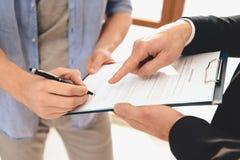 Agent immobilier avec la famille en nouvel appartement avec des boîtes en carton Le mari signe le contrat photo libre de droits