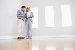 Agent immobilier blond concentré montrant une salle et quelques documents à images stock