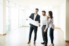 Agent immobilier discutant la disposition d'appartement avec des couples dans la chambre vide images libres de droits