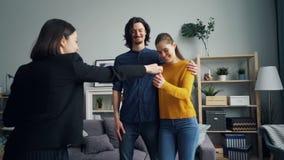 Agent immobilier donnant la clé à de nouveaux propriétaires se serrant la main, couples heureux embrassant et étreignant banque de vidéos