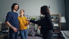 Agent immobilier donnant la clé à la fille et le type se serrant la main, propriétaires heureux embrassant étreindre banque de vidéos