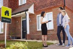 Agent immobilier en dehors de Chambre à vendre avec de jeunes couples image stock