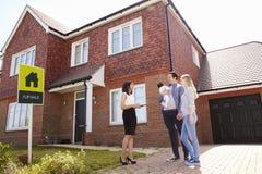 Agent immobilier en dehors de Chambre à vendre avec la jeune famille photo libre de droits