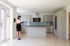 Agent immobilier femelle dans l'évaluation de mise en oeuvre de cuisine images libres de droits