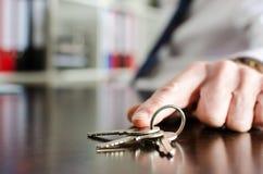 Agent immobilier montrant des clés de maison Photo libre de droits