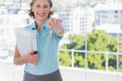 Agent immobilier montrant des clés de maison et souriant à l'appareil-photo Images stock