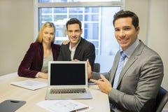 Agent immobilier présentant un nouveau projet sur l'ordinateur portable, jeune coup Images stock