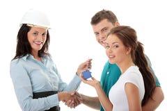 Agent immobilier réel et jeunes couples Photo libre de droits
