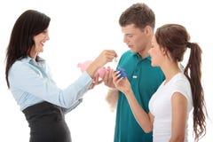 Agent immobilier réel et jeunes couples Photos stock