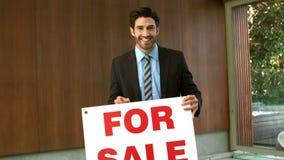 Agent immobilier réel heureux avec le signe vendu banque de vidéos