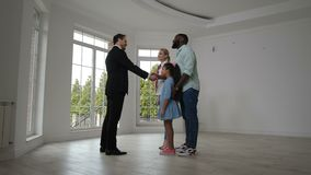Agent immobilier satisfaisant donnant des clés de maison aux propriétaires d'une maison banque de vidéos