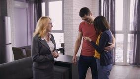 Agent immobilier supérieur donnant les touches début d'écran aux couples clips vidéos