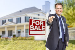 Agent with Keys in Front of Sale Sign and House. Real Estate Agent with House Keys in Front of For Sale Sign and Home Royalty Free Stock Photography