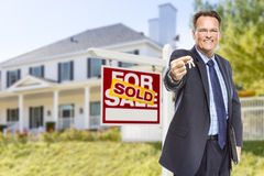 Agent with Keys in Front of Sold Sign and House. Real Estate Agent with House Keys in Front of Sold Sign and Home Stock Photos