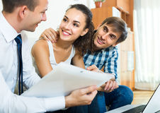 Agent with laptop and young couple Stock Photos