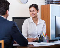 Agent listening to customer and smiling in agency Royalty Free Stock Photo