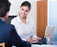 Agent listening to customer and smiling in agency Stock Photography
