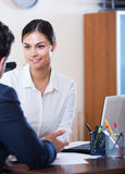 Agent listening to customer and smiling in agency Royalty Free Stock Photography
