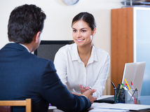 Agent listening to customer and smiling in agency Royalty Free Stock Photos