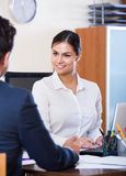 Agent listening to customer and smiling in agency Stock Photo