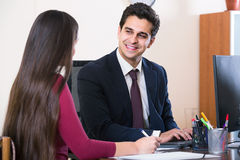 Agent listening to customer and smiling in agency Stock Photos