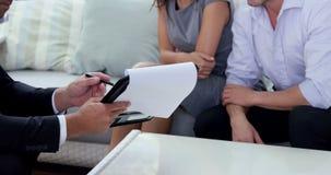 Agent montrant le contrat aux couples banque de vidéos