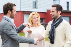 Agent nieruchomości dostarcza klucze młoda atractive para Obraz Stock