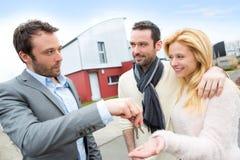 Agent nieruchomości dostarcza klucze młoda atractive para Fotografia Stock