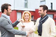 Agent nieruchomości dostarcza klucze młoda atractive para Zdjęcie Stock