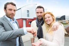Agent nieruchomości dostarcza klucze młoda atractive para Obrazy Royalty Free