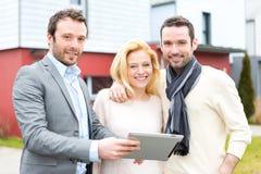 Agent nieruchomości i młoda para przed ich następnym domem Obrazy Stock