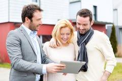 Agent nieruchomości i młoda para przed ich następnym domem Zdjęcie Stock