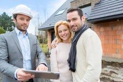 Agent nieruchomości i młoda para przed przyszłość domem Zdjęcia Stock