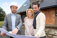 Agent nieruchomości i młoda para przed przyszłość domem Zdjęcie Stock