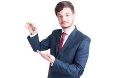 Agent nieruchomości jest ubranym kostium pokazuje wpisywać Zdjęcie Stock