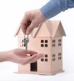 Agent nieruchomości oddawał majątkowych lub nowych domowych klucze klient na bielu Fotografia Royalty Free