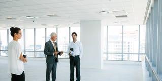 Agent nieruchomości opowiada z klientami wśrodku pustego biura sp Fotografia Royalty Free