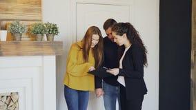 Agent nieruchomości spotyka szczęśliwej pary małżeńskiej, pokazuje papiery i mówi one o mieszkaniu, Młodzi ludzie są zdjęcie wideo