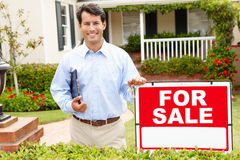 Agent nieruchomości trwanie outside dom Fotografia Stock