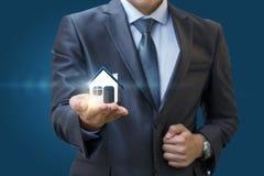 Agent nieruchomości trzyma wzorcowego dom w ręce Fotografia Stock